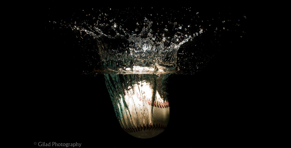 A baseball being dropped into a fishtank