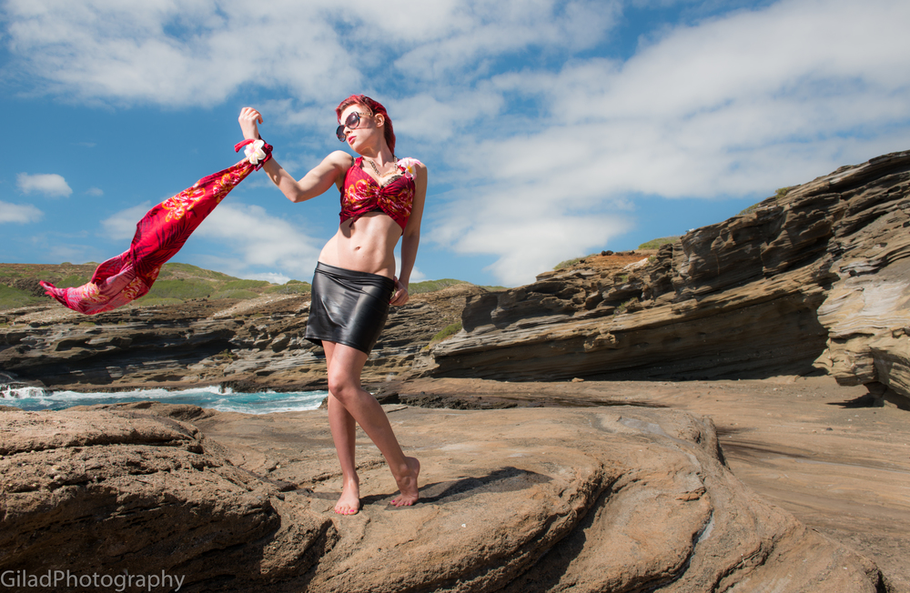 A model poses with a red handkerchief on a rocky beach