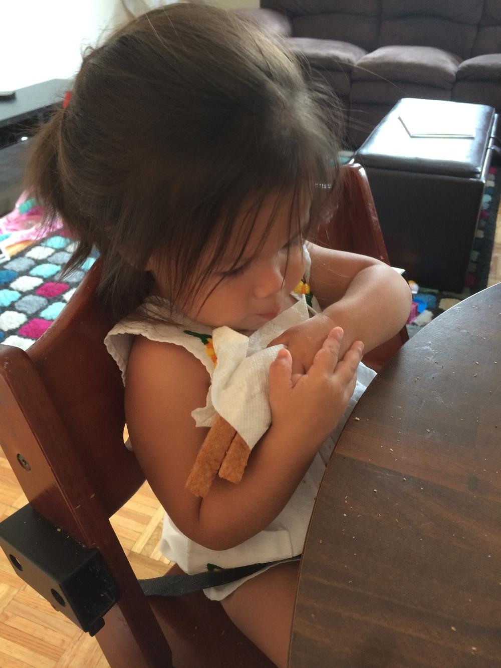 Swaddling her sandwich