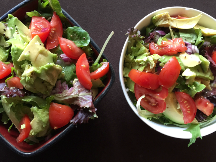 This salad has spring mix, tomatoes, avocados and red onion