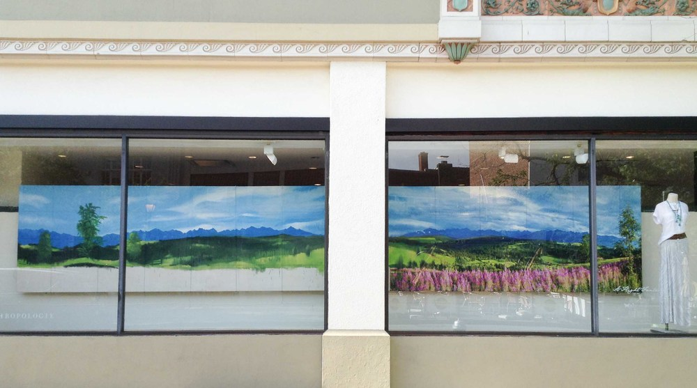 Two massive canvas frames were constructed from 2x3 lumber and then stretched with canvas and hung in the window. The photo mural was mirrored and painted grid by grid  using latex paint mixed with joint compound for thickness.