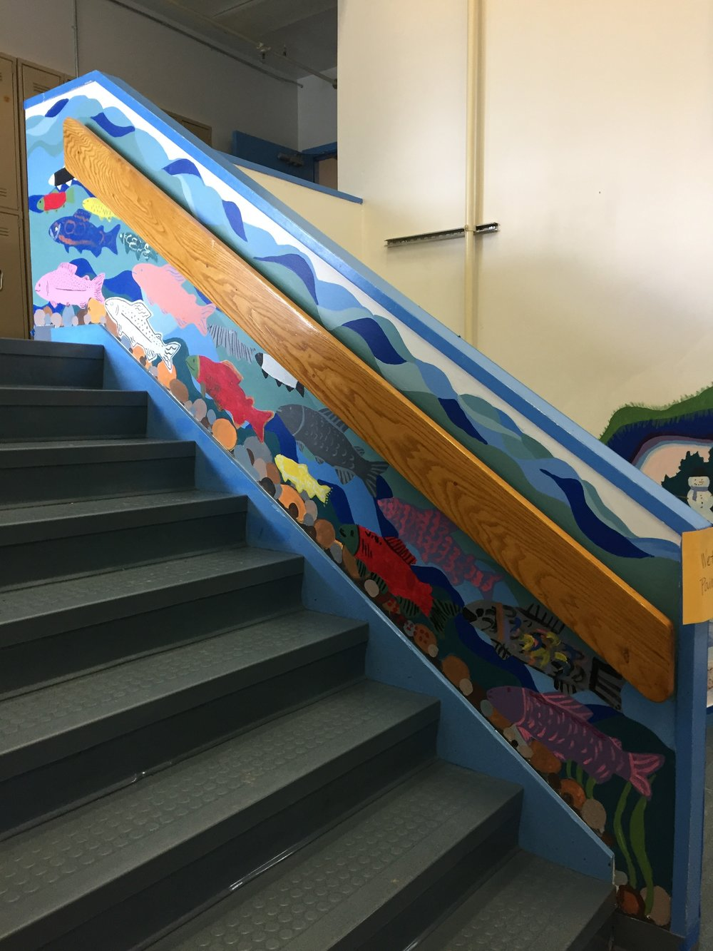The wall of fish going up the stairs. The students gather here each morning for a school meeting.
