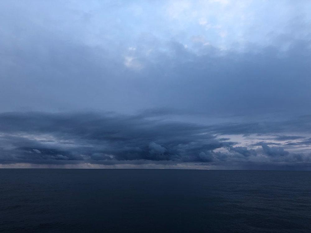 Clouds gathering (above) and waves crashing (below)