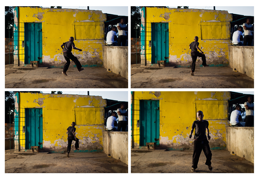 Boy dancing outside his parents shop, Mozambique