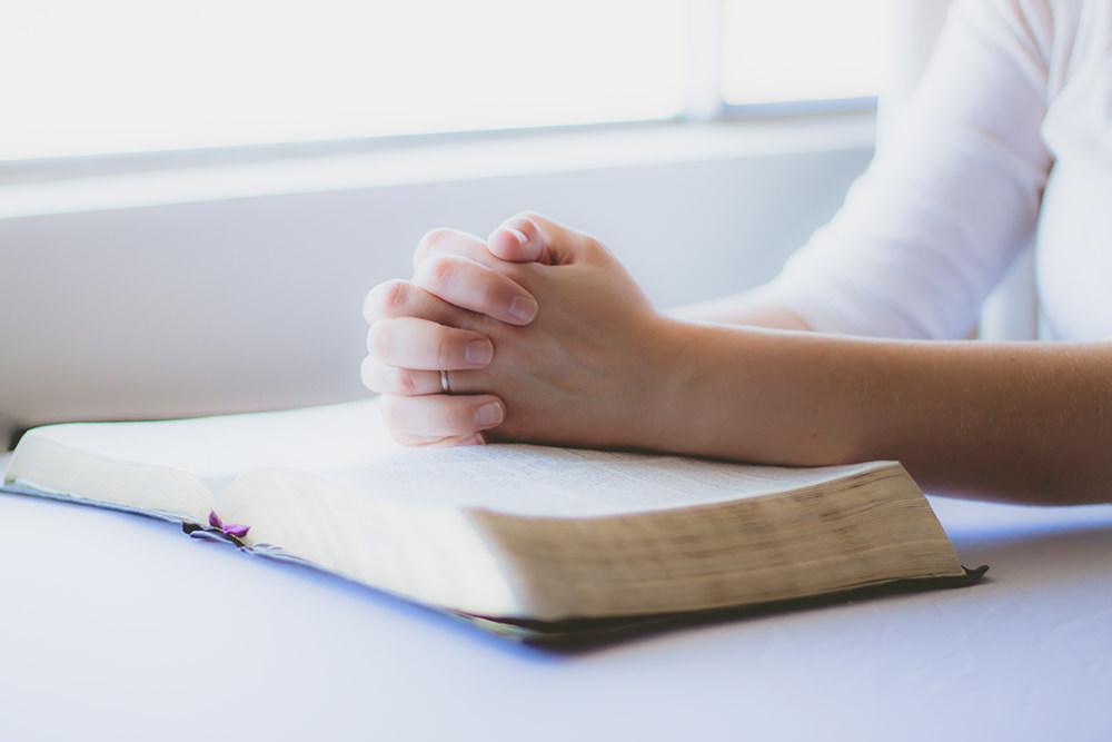 Foto gratis de mujer cristiana orando con Biblia abierta