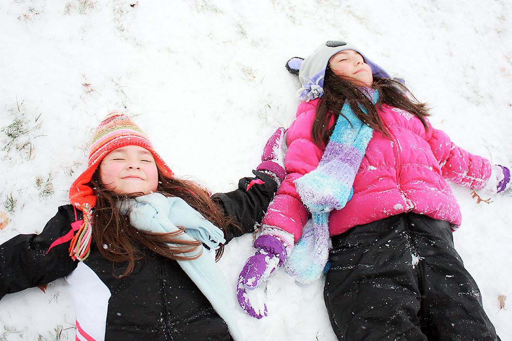 Foto gratis de dos niñas descansando en la nieve