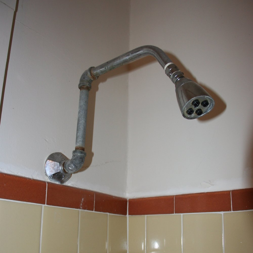 "A previous homeowner ""saved"" money by adding multiple pipes to raise this shower head"