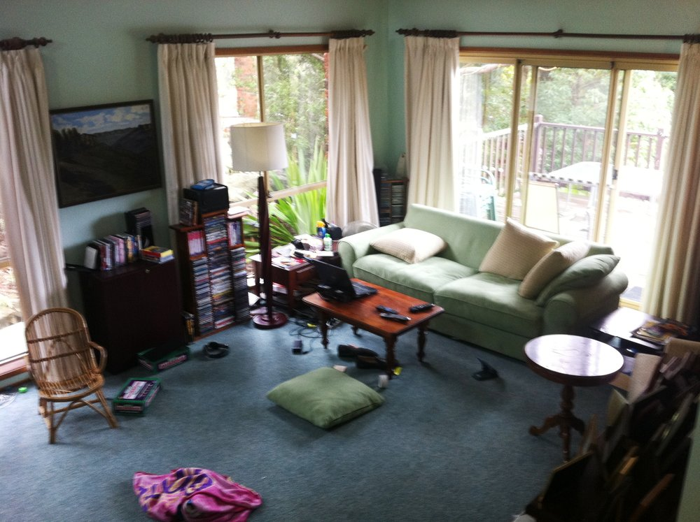 Living Room View One: a lot of cluttered space and walls with mouldy furniture.