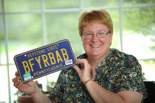 """Karen Foard holds her license plate which in short says """"breast feed your baby"""". Karen Foard is a International Board Certified Lactation Consultant (IBCLC). Foard has been supporting, promoting, and educating people on breast feeding for the last 25 years.  NABIL K. MARK — CDT photo"""