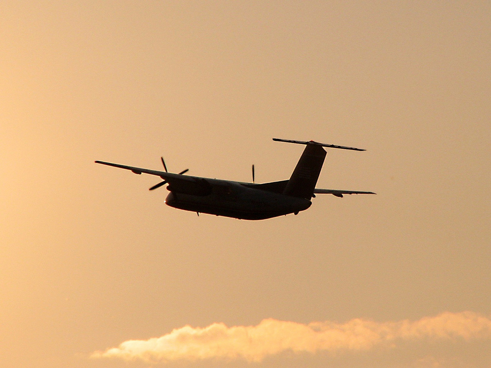 A Dash 8 flies off into the sunset at SWF