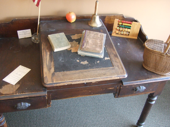 The teacher's desk was used in Bedford High School by Mrs. Hockersmith. The abacus is a reproduction of similar tools used  to help students learn to count. A school bell on the desk would have been wrung to bring students to attention. The glass inkwell stored ink for the teacher to use.