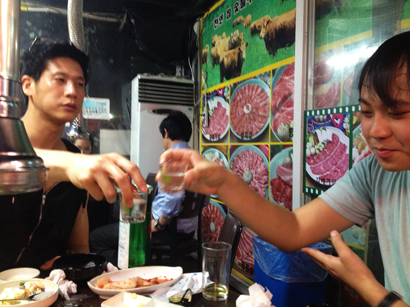 Jun (right) clinks soju glasses with his boss Dohoon (left). Dohoon is both older and Jun's boss, it's important for Jun to show respect by touching his elbow with his hand. Note that Dohoon doesn't do this.
