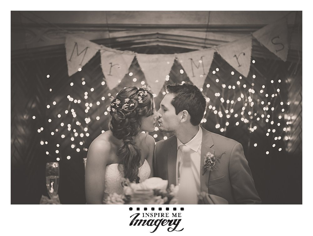 A quick kiss at the sweetheart table in front of their beautiful decor. We wish them all the best.