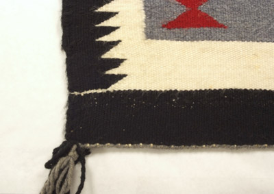 here's a closer look at a white ch'ihónít'i that the weaver deliberately extended across the black edge of this rug.