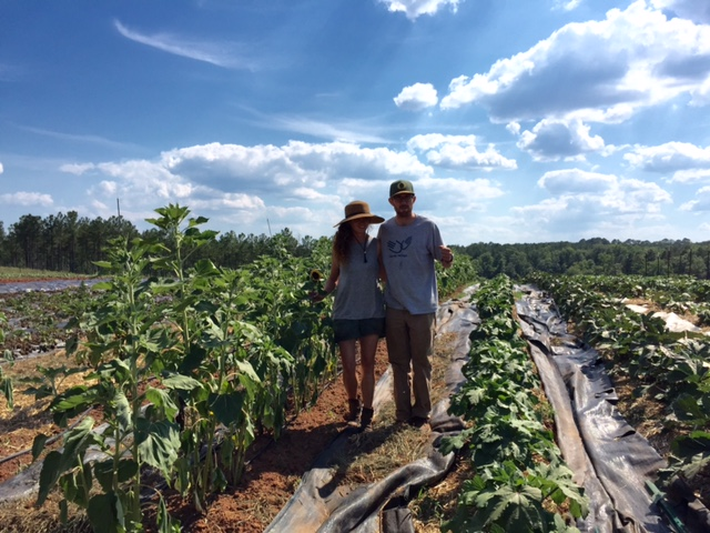 Mary-Martin and Ian standing with sunflowers and baby okra plants.