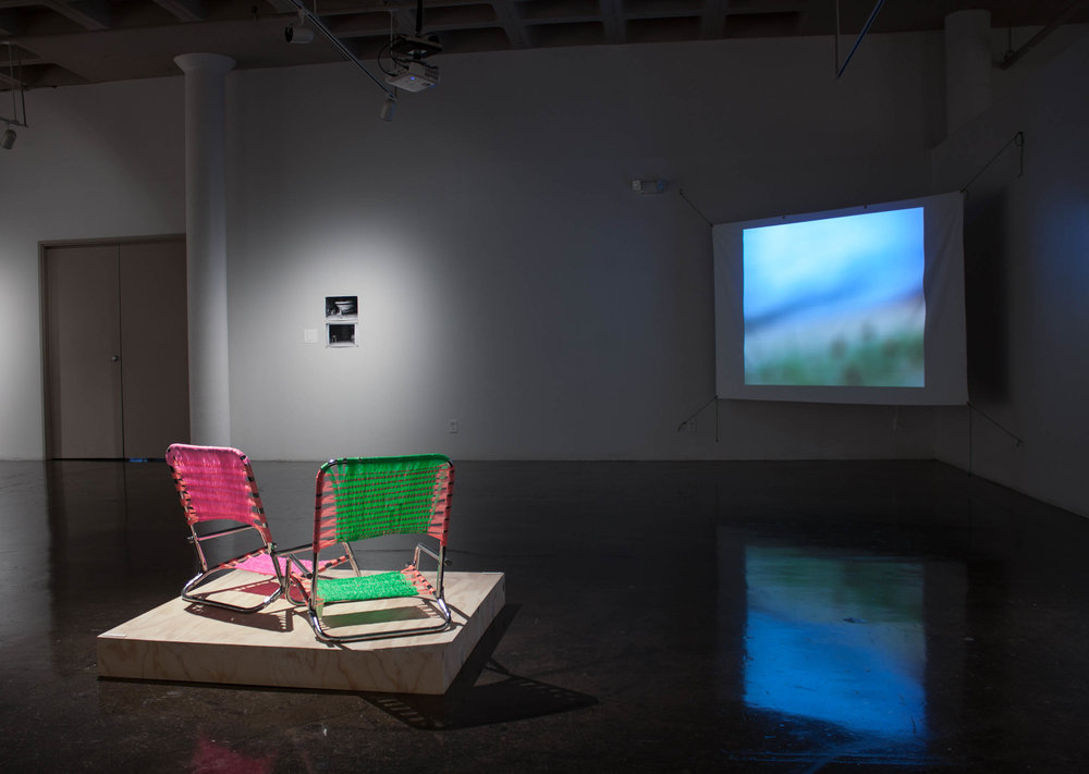 Installation view at SSA in 2017 of    Shorelines (from the back porch), 2015 , 2 found chairs, flagging tape  &   A wave , 2017, Video installation with blackout cloth and nylon rope, 4 minutes 33 seconds