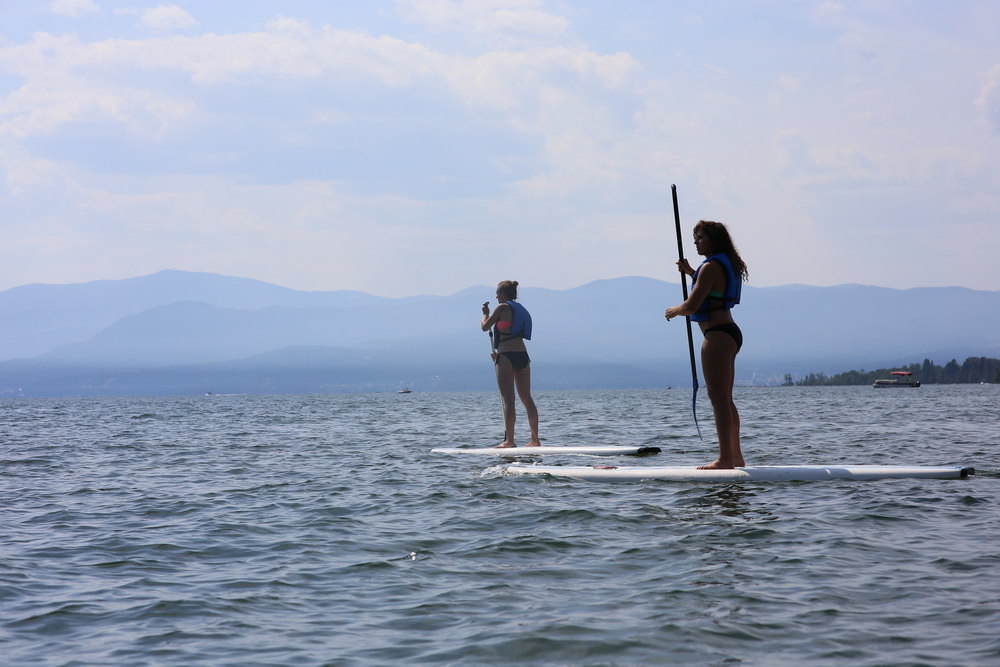 8/9/14  |Sarah Smith and Sarah Al-Khayyal take a break from railroading to paddle board Flathead Lake in Whitefish, MT.  (Credit: Tyler Metcalfe, National Geographic Travel)