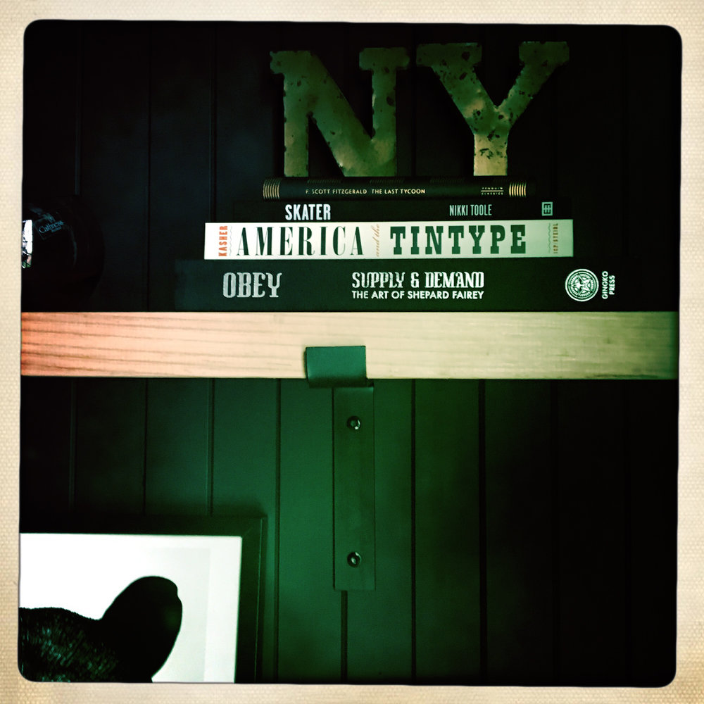 Black Steel Shelf Brackets On Wall With Books And New York Sign