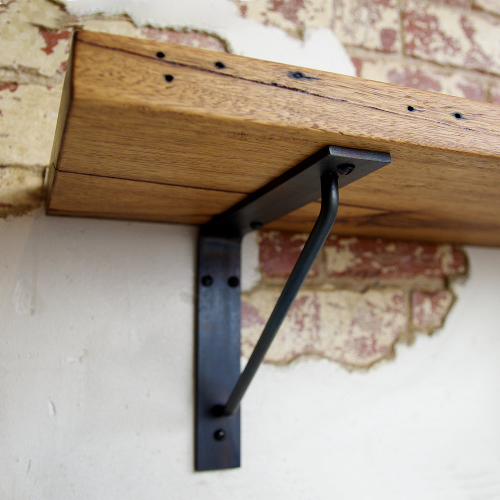 Black steel shelf bracket on brick wall with wood shelf.