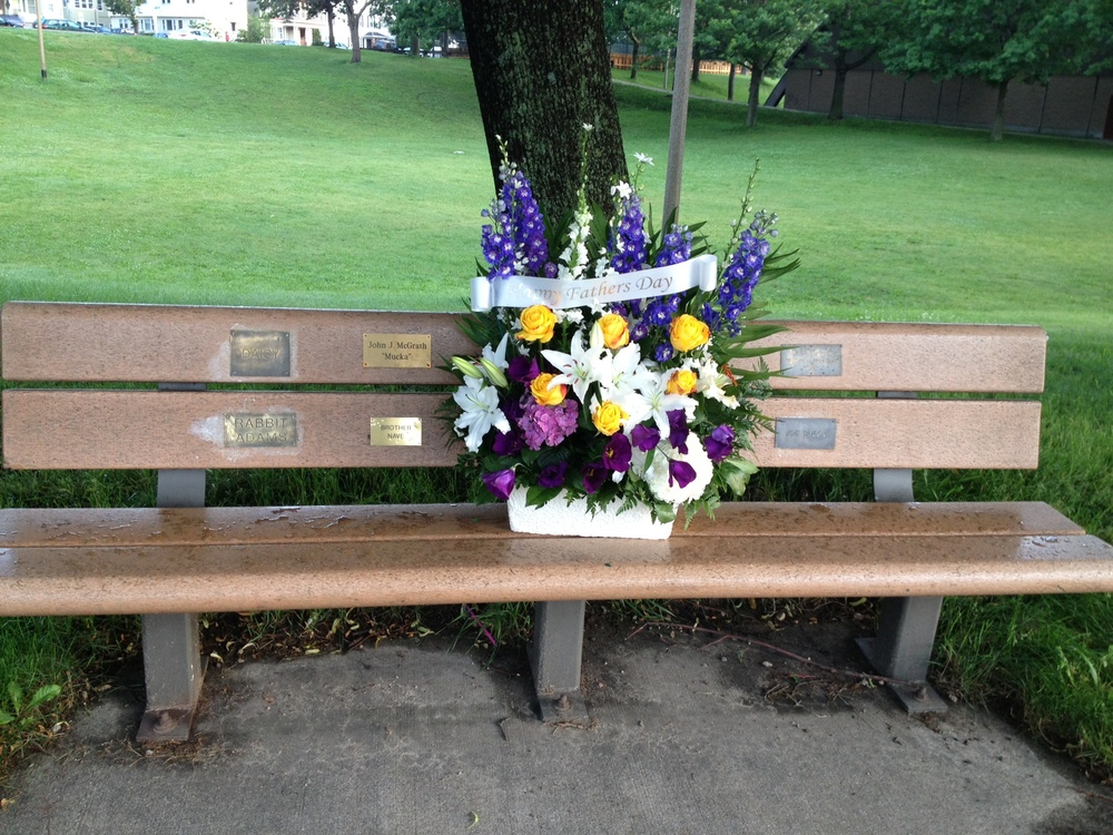 Father's Day flowers on memorial bench.