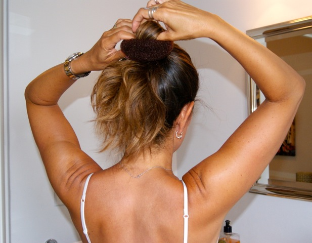 Step 1: Gather hair into a ponytail and fasten with an elastic. Pull the ponytail through the hole in the bun maker and slide up the ponytail base.