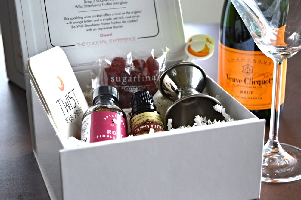 """Rose Colored Glasses"" kit by Twist Your Spirits. Contains Royal Rose Syrup, SCRAPPY's Orange bitters, SUGARFINA Wild Strawberry Fruttini, One Jigger, Two Cocktail Stirrers and Two Coasters. Serves 4."