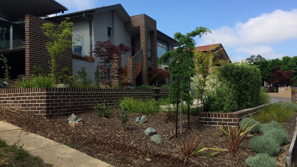 Hughes Residence   In the lead up to a big occasion this family resolved to get in place the gardens they had always wanted. Terracing the steep block with retaining walls to match the house, and use of lush multi-textured plantings now provides an oasis away from busy work lives.