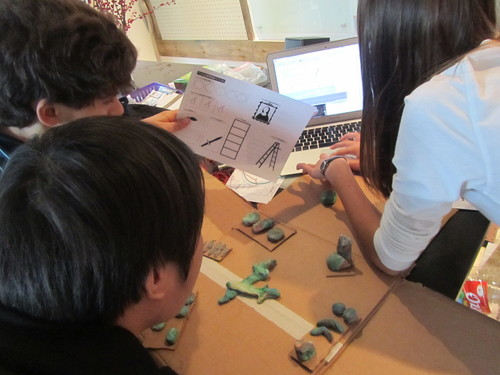 Prototyping with the worksheet, Play Doh, and a cardboard model of the room.