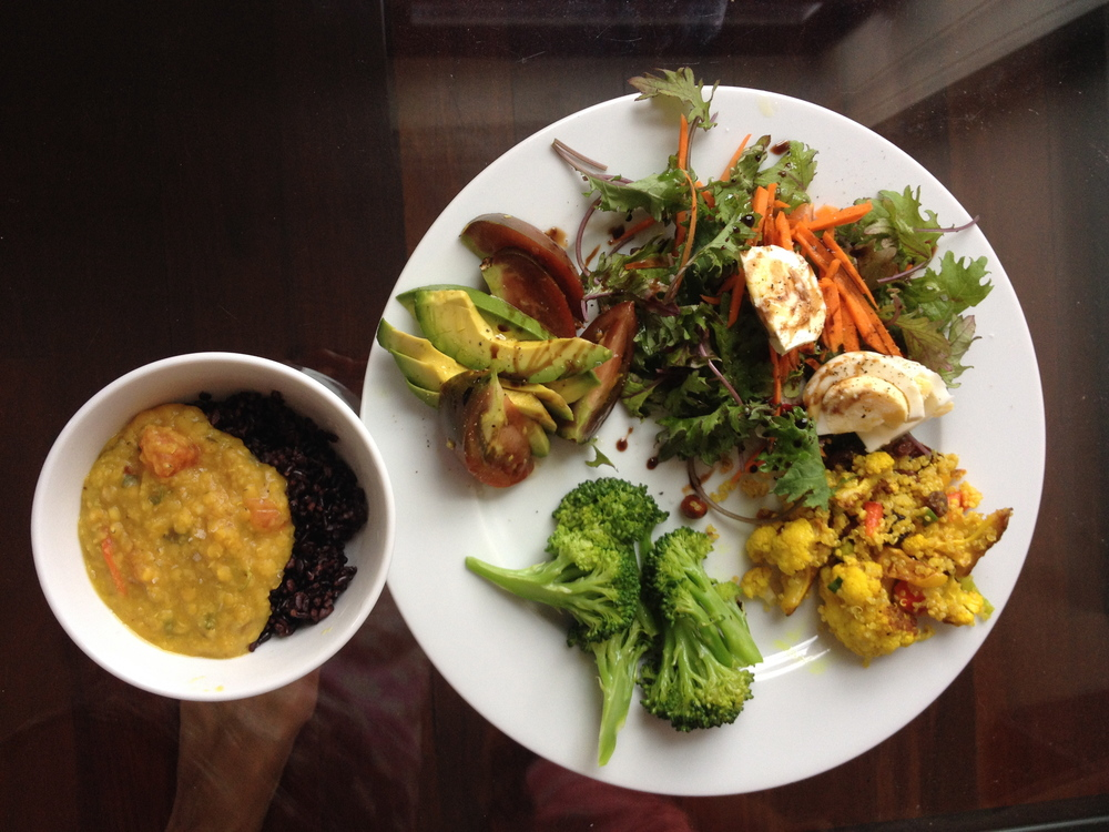 Small bowl of dal and purple rice, steamed broccoli with sesame oil, curried cauliflower and quinoa, salad with baby kale, carrots and boiled egg, avocado and heirloom tomatoes drizzled with lime-infused olive oil and lavender balsamic vinegar.
