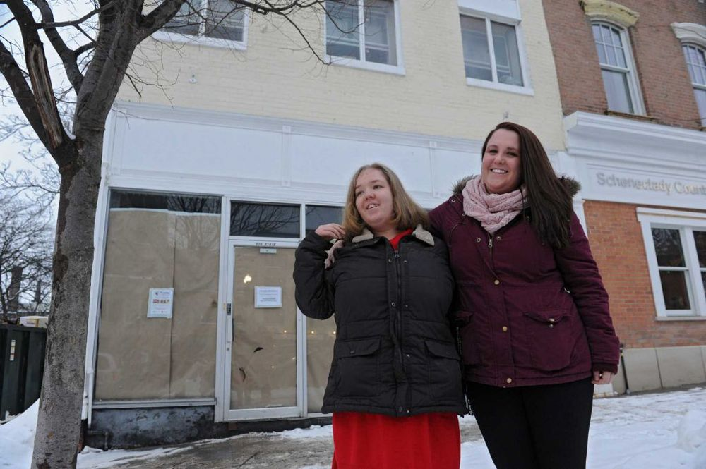 Sara Mae Hickey, right, founder and president of The Autism Initiative, stands with her sister Emily in front of the construction site for Puzzles Bakery & Cafe on State St. on Wednesday, Feb. 19, 2014, in Schenectady, N.Y. The cafe, which will open in the Spring, will be a place for adults with autism to work. Sara Mae's sister is on the autism spectrum. (Lori Van Buren / Times Union)