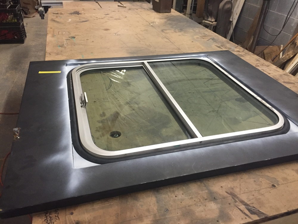 More work than it looks - steel frame and steel sheet, all welded and ground down to a smooth seam on inner and outer edges. The reclaimed aluminum-framed sliding window was fit in with new gasket after a lot of re-grinding.