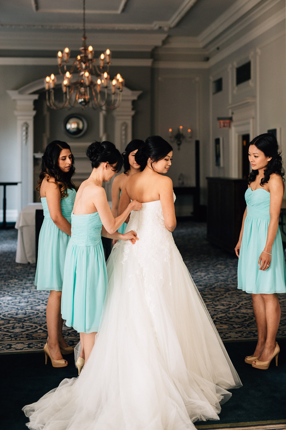 putting on the wedding dress at the vancouver club bride bridesmaids photography