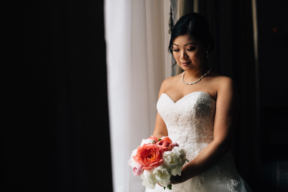 bride by window at the vancouver club in coal harbour wedding photography