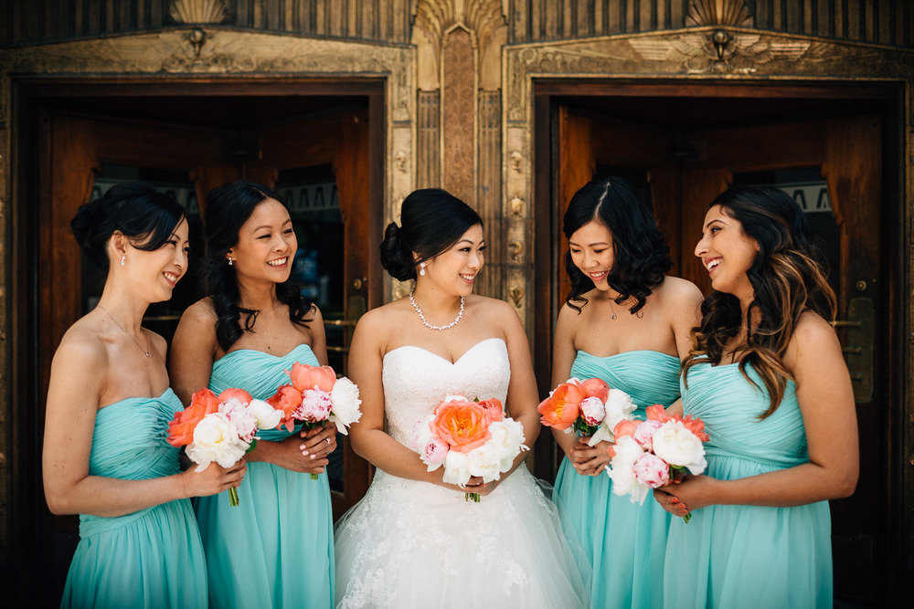 bridesmaids candid laughter in front of marine building in vancouver wedding photography