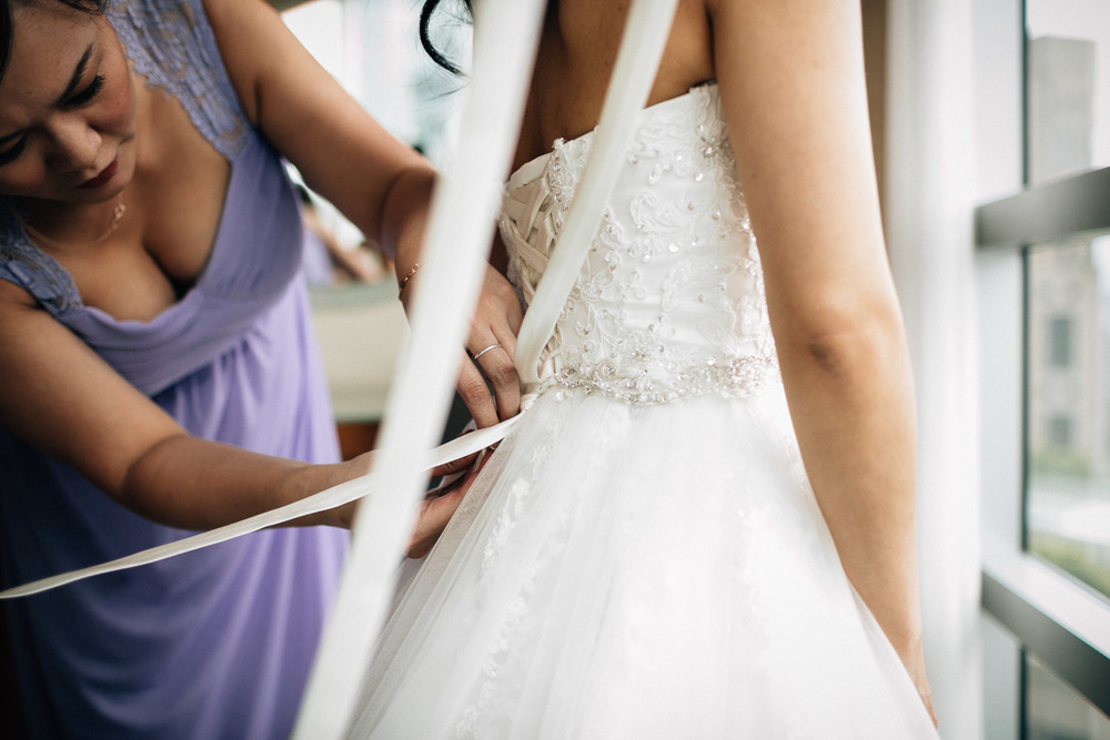 bridesmaid helping bride put on wedding dress at the westin grand hotel