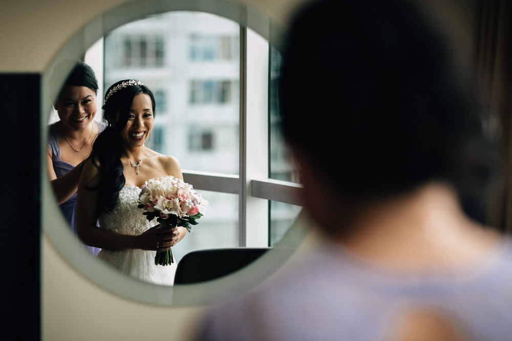 maid of honour helping bride get ready at the westin grand hotel in vancouver