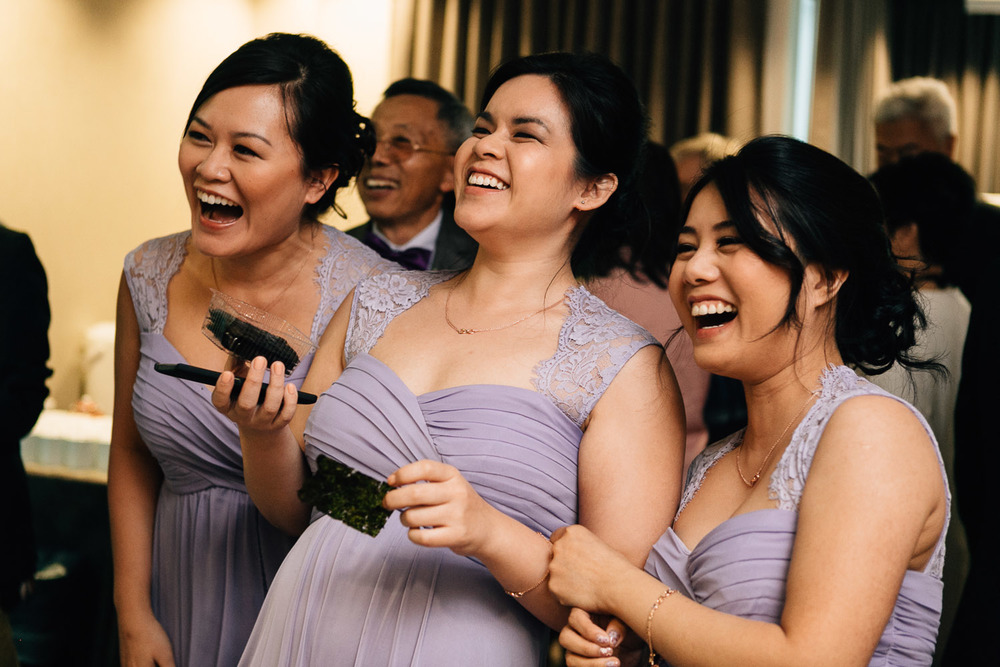 bridesmaids laughing candid asian door games wedding photography in vancouver