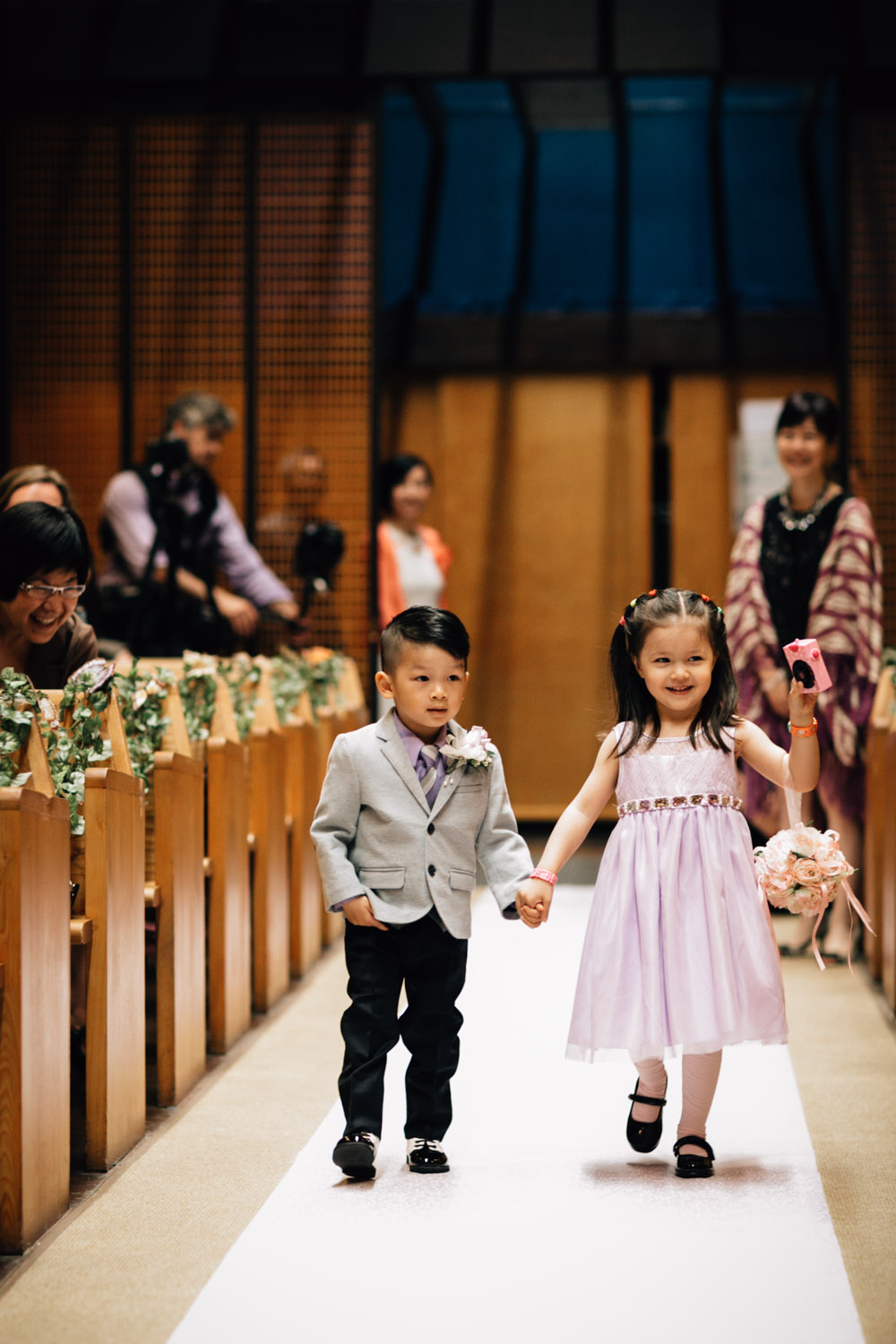 ring bearer and flower girl walk down aisle of redeemer lutheran church vancouver wedding photography