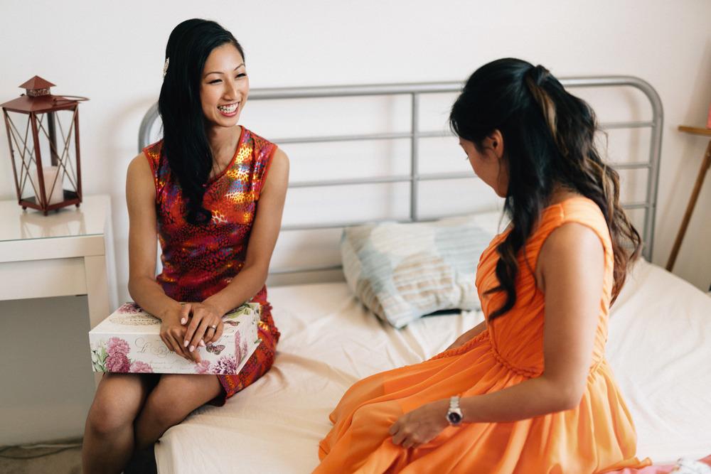 asian bride giving gift to bridesmaid vancouver wedding photographer