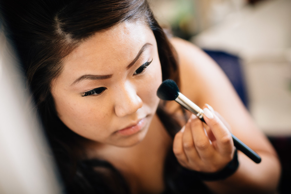 asian bride putting on makeup for wedding in surrey photography