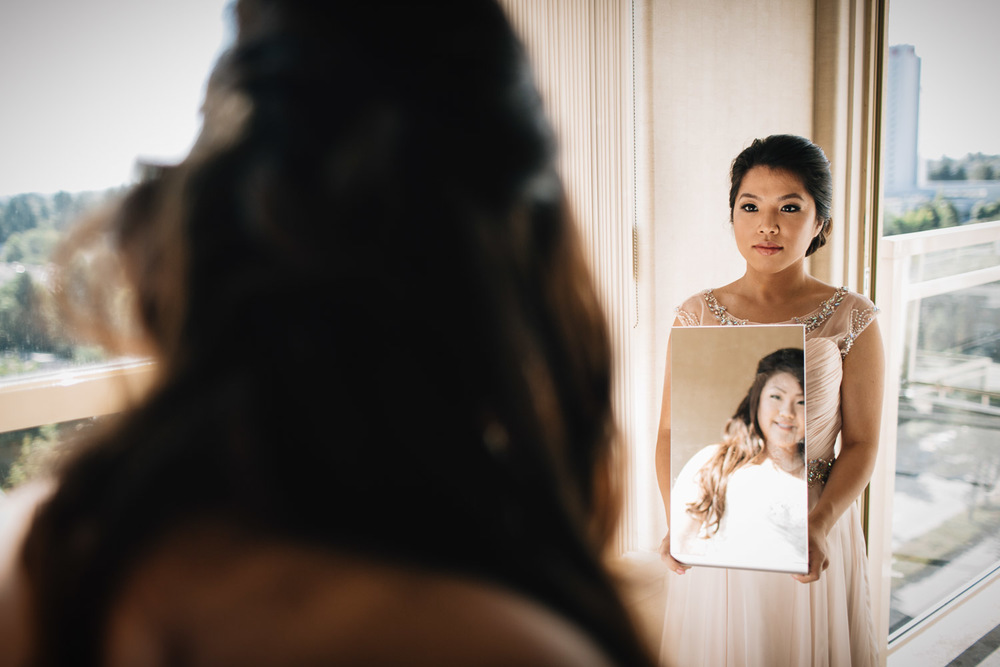 bride looking in mirror in surrey sandman hotel for wedding photography