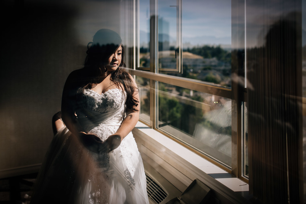 asian bride looking out sandman hotel window for wedding in surrey