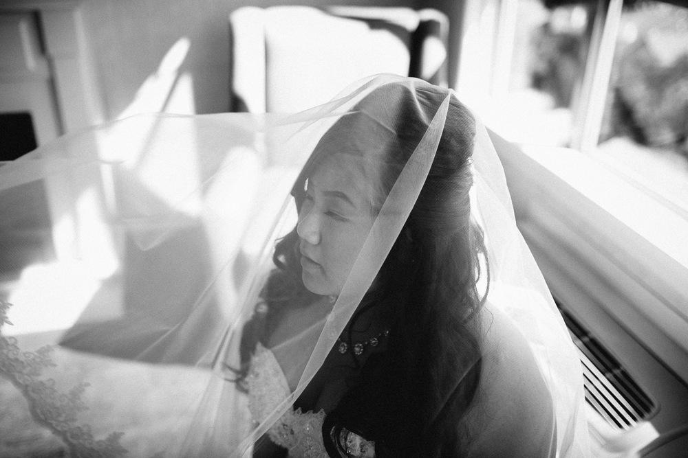 surrey wedding photography bride putting on veil