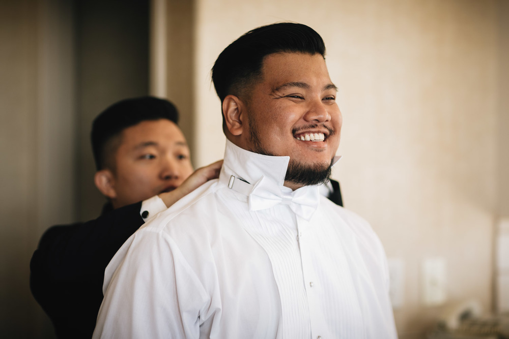 asian groom getting ready in surrey sandman hotel wedding