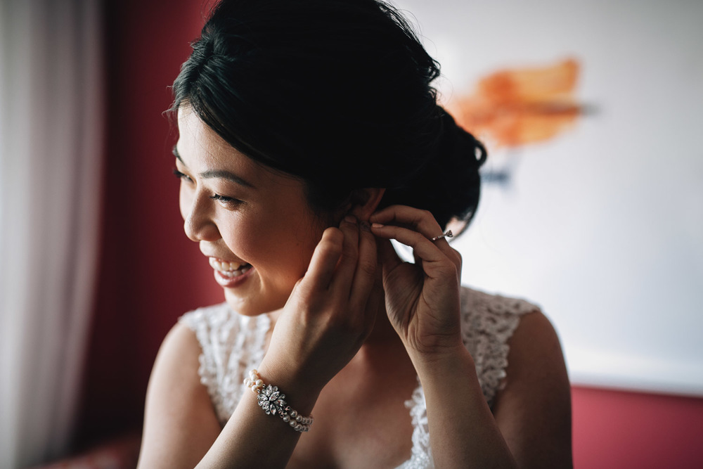 bride putting on earrings for wedding in yaletown vancouver bc photography