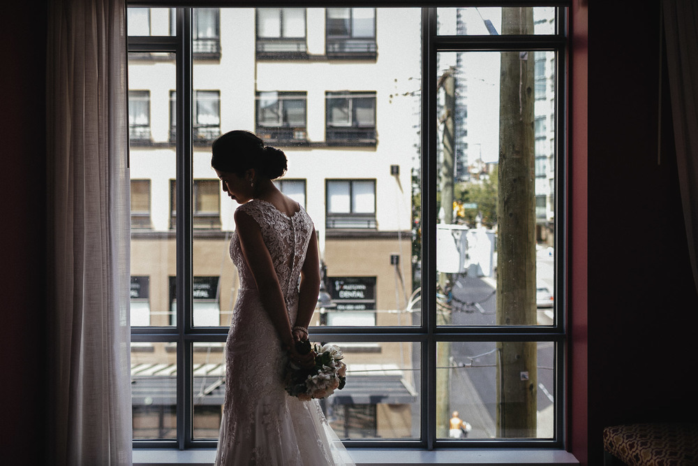 bride by window in opus hotel yaletown vancouver bc wedding photography