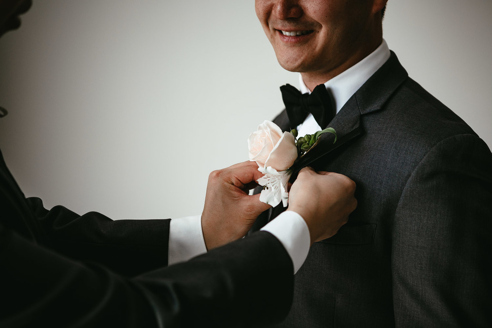putting on boutonniere  for groom in vancouver wedding photography
