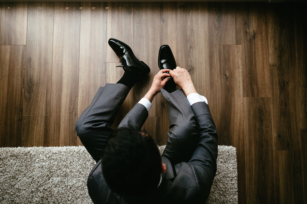 groom putting on shoes before wedding ceremony in vancouver bc