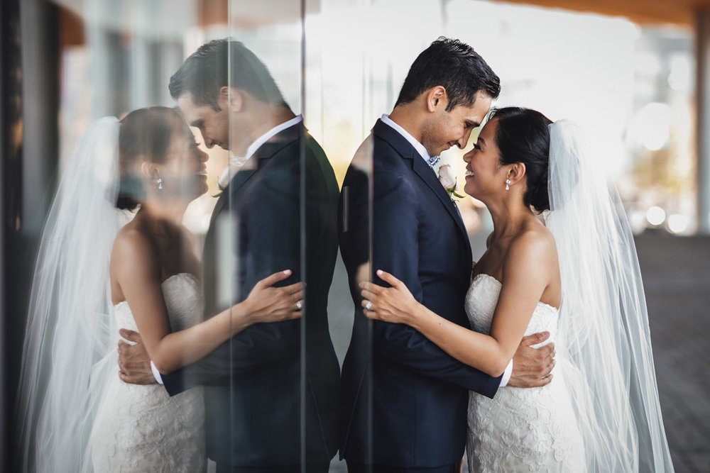 bride and groom glass reflection at convention centre in vancouver bc