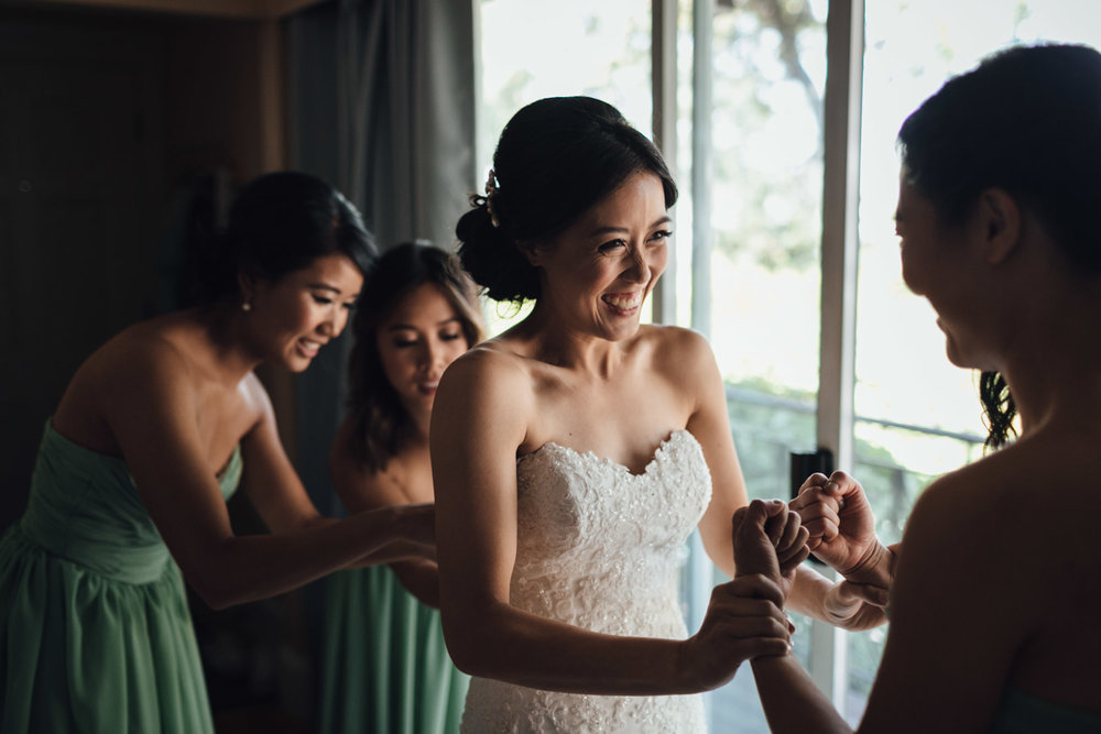 bride putting on wedding dress in vancouver wedding photographer